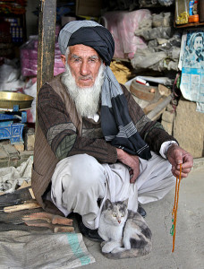 An Afghan elder sits with his cat outside his store.